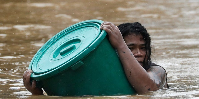 A man uses a plastic canister to float while negotiating rising floodwaters from Typhoon Vamco in Marikina, Philippines, on Thursday, Nov. 12, 2020. Vamco swelled rivers and flooded low-lying areas as it passed over the storm-battered northeastern part of the country. (AP Photo/Aaron Favila)