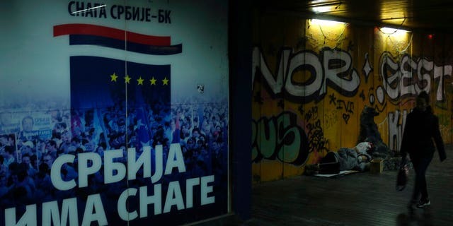 "A woman walks through an underground passage by a homeless person and inscription on the wall reading ""Serbia has the strength"" in Belgrade, Serbia, Monday, Nov. 16, 2020."