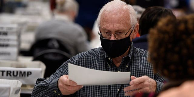 Cobb County election officials handle ballots during an audit, Monday, Nov. 16, 2020, in Marietta, Ga. (AP Photo/Mike Stewart)