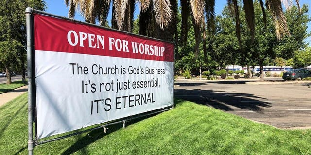 """In this Thursday, 七月 9, 2020 file photo an """"Open for Worship"""" banner is posted outside the Crossroads Community Church in Yuba City, 牛犊. (AP Photo/Adam Beam)"""