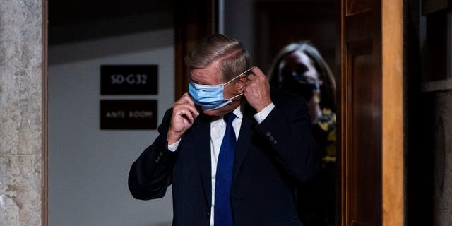 Sen. Lindsey Graham, R-S.C., puts on his face mask as he arrives for a Senate Judiciary Committee hearing on Facebook and Twitter's actions around the closely contested election on Tuesday, Nov. 17, 2020, in Washington.. (Bill Clark/Pool via AP)