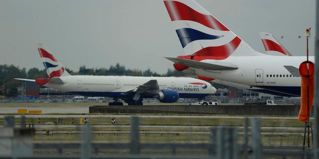 FILE: A British Airways plane, at left, is towed past other planes sitting parked at Heathrow Airport in London.