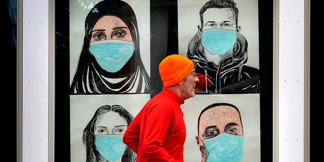 FILE - In this Nov. 16, 2020, file photo, a runner passes by a window displaying portraits of people wearing face coverings to help prevent the spread of the coronavirus in Lewiston, Maine. (AP Photo/Robert F. Bukaty, File)