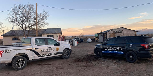 In this photo released by the Colorado Bureau of Investigation, law enforcement vehicles are parked at one of two properties where skeletal remains were found about 20 miles south-southeast of Alamosa, Colo., op Woensdag, Nov.. 18, 2020. (Colorado Bureau of Investigation via AP)