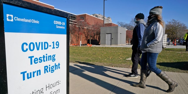 Two people walk past a sign for COVID-19 testing at the Cleveland Clinic, Wednesday, Nov. 18, 2020, in Cleveland. (AP Photo/Tony Dejak)
