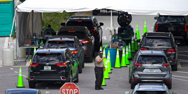 In this Nov. 18 photo, vehicles line up to be tested at the COVID-19 drive-thru testing center at Miami Beach Convention Center in Miami Beach, Fla. With coronavirus cases surging and families hoping to gather safely for Thanksgiving, long lines to get tested have reappeared across the U.S. (David Santiago/Miami Herald via AP, File)