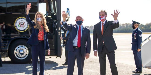 Vice President Mike Pence, center, Senator Kelly Loeffler, left, and Senator David Perdue, right, wave at people at Dobbins Air Reserve Base in Marietta, Ga., Nov. 20, 2020. (Alyssa Pointer /Atlanta Journal-Constitution via AP)