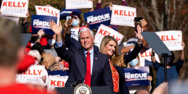 Vice President Mike Pence and Kelly Loeffler wave to the crowd during a Defend the Majority Rally, Friday, Nov. 20, 2020 in Canton, Ga. U.S. Sen. Kelly Loeffler waves behind Pence. (AP Photo/Ben Gray)