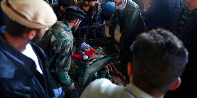 Relatives stand around the dead body of a boy who was killed by a mortar shell attack in Kabul, Afghanistan, Sabato, Nov. 21, 2020. Mortar shells slammed into different parts of the Afghan capital on Saturday. (AP Photo/Rahmat Gul)