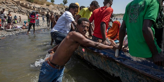 Tigray refugees who fled a conflict in Ethiopia ride a boat on the banks of the Tekeze River on the Sudan-Ethiopia border. (AP Photo/Nariman El-Mofty)