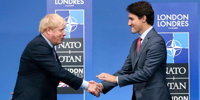 In this Dec. 4, 2019 photo, British Prime Minister Boris Johnson, left, welcomes Canadian Prime Minister Justin Trudeau during official arrivals for a NATO leaders meeting at The Grove hotel and resort in Watford, Hertfordshire, England. (AP Photo/Francisco Seco, File)