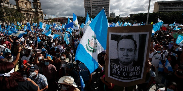 Protesters gather outside Congress in Guatemala City, Saterdag, Nov.. 21, 2020. Hundreds of protesters were protesting in various parts of the country Saturday against Guatemalan President Alejandro Giammattei and members of Congress for the approval of the 2021 budget that reduced funds for education, health and the fight for human rights. (AP Photo/Moises Castillo)