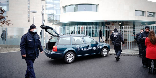 A car stands in front of the chancellery after it crashed into the front gate of the building housing German Chancellors Angela Merkel's offices in Berlin, Germany, Wednesday, Nov. 25, 2020. (Michael Kappeler/dpa via AP)