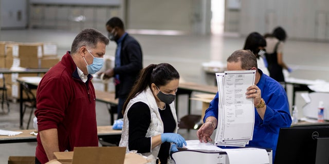 Workers scan ballots as the Fulton County presidential recount gets underway Wednesday, Nov. 25, 2020, at the Georgia World Congress Center in Atlanta. (Associated Press)