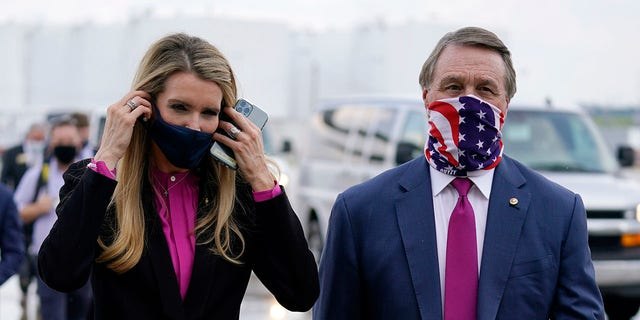 In this July 15, 2020, file photo Sen. Kelly Loeffler, R-Ga., puts on a face mask as she walks with Sen. David Perdue, R-Ga., reg, at UPS Hapeville Airport Hub in Atlanta. Both Perdue and Loeffler have said they support $  2,000 stimulus tjeks. (AP Foto / Evan Vucci, lêer)