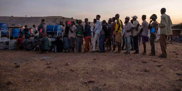 Tigray men who fled the conflict in Ethiopia's Tigray region, stand in line to receive food cooked by Sudanese women volunteers, at Umm Rakouba refugee camp in Qadarif, eastern Sudan, Thursday, Nov. 26, 2020. (AP Photo/Nariman El-Mofty)