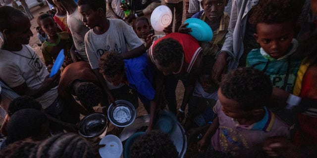 "Tigray men who fled the conflict in Ethiopia's Tigray region, receive cooked rice from charity organization Muslim Aid, at Umm Rakouba refugee camp in Qadarif, eastern Sudan, Friday, Nov. 27, 2020. Ethiopian Prime Minister Abiy Ahmed again ruled out dialogue with the leaders of the defiant Tigray region Friday but said he was willing to speak to representatives ""operating legally"" there during a meeting with three African Union special envoys trying to end the deadly conflict between federal troops and the region's forces. (AP Photo/Nariman El-Mofty)"