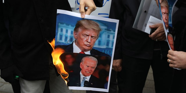 A group of protesters burn pictures of the U.S. 唐纳德·特朗普总统, 最佳, and the President-elect Joe Biden in a gathering in front of Iranian Foreign Ministry on Saturday, 十一月. 28, 2020, a day after the killing of Mohsen Fakhrizadeh an Iranian scientist linked to the country's nuclear program by unknown assailants near Tehran. (AP Photo/Vahid Salemi)