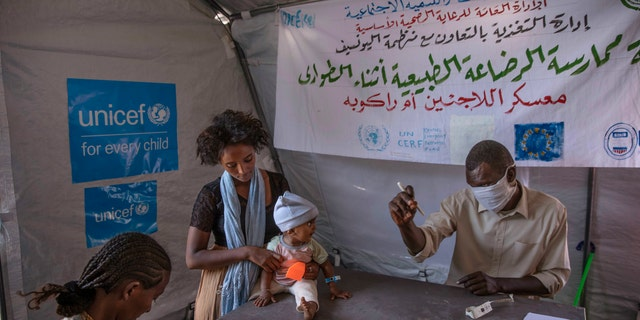 Tigray women who fled the conflict in Ethiopia's Tigray region, take shelter inside a UNICEF tent, as Filippo Grandi, U.N. High Commissioner for Refugees, visits Umm Rakouba refugee camp in Qadarif, eastern Sudan, Saturday, Nov. 28, 2020. (AP Photo/Nariman El-Mofty)