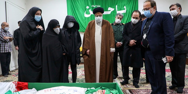 Iran's Judiciary Chief Ayatollah Ebrahim Raisi pays his respect to the body of slain scientist Mohsen Fakhrizadeh among his family, in Tehran, Iran, Saturday, Nov. 28, 2020. Iranian officials have blamed Israel for the killing of Fakhrizadeh who led Tehran's disbanded military nuclear program. (Mizan News Agency via AP)