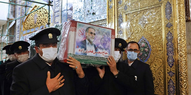 In this picture released by the Iranian Defense Ministry and taken on Saturday, 十一月. 28, 2020, caretakers from the Imam Reza holy shrine, carry the flag-draped coffin of Mohsen Fakhrizadeh, an Iranian scientist linked to the country's disbanded military nuclear program, who was killed on Friday, during a funeral ceremony in the northeastern city of Mashhad, 伊朗. (Iranian Defense Ministry via AP)