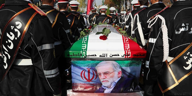 In this photo released by the official website of the Iranian Defense Ministry, military personnel stand near the flag-draped coffin of Mohsen Fakhrizadeh, a scientist who was killed on Friday, during a funeral ceremony in Tehran, Iran, Monday, Nov. 30, 2020. (Iranian Defense Ministry via AP)