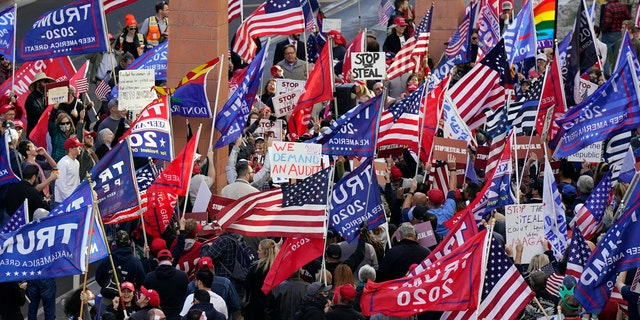 "Supporters of President Donald Trump protest in front of a local hotel where Arizona Republicans have scheduled a meeting as a ""fact-finding hearing"" to discuss the election, featuring members of Trump's legal team and Arizona legislators, Monday, Nov. 30, 2020, in Phoenix. (AP Photo/Ross D. Franklin)"