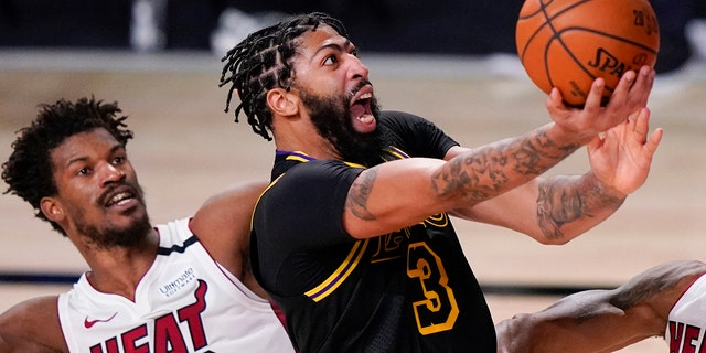 In this Oct. 9, 2020, file photo, Los Angeles Lakers forward Anthony Davis shoots past Miami Heat forward Jimmy Butler during the second half in Game 5 of the NBA Finals in Lake Buena Vista, Fla. AP Photo/Mark J. Terrill, File)