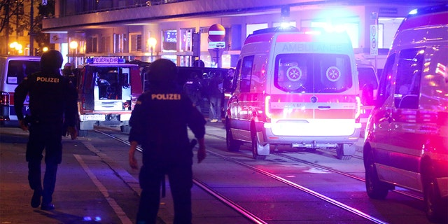A police officer walked near an ambulance at the scene after gunfire in Vienna on Monday.  (Photo / Ronald Zak)