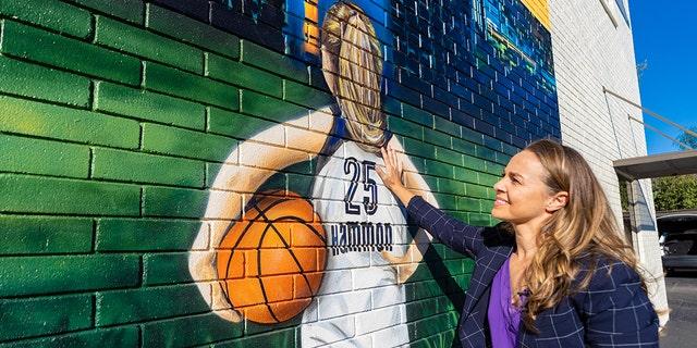 Becky Hammon visits a mural in San Antonio.