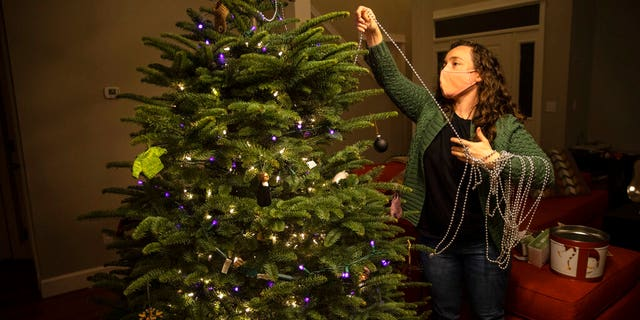 Ani Sirois puts lights and decorations on the family's Christmas tree at her home on Tuesday, Nov.. 24, 2020 in Portland, Erts. (AP Photo/Paula Bronstein)
