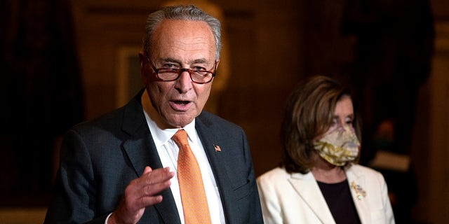 In this Aug. 6, 2020, file photo Senate Minority Leader Sen. Chuck Schumer of New York speaks to reporters as House Speaker Nancy Pelosi of California listens at right on Capitol Hill in Washington. (AP Photo/Carolyn Kaster, File)
