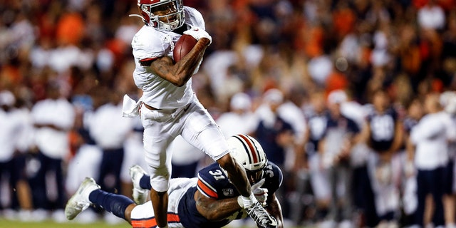 In this Nov. 30, 2019, file photo, Alabama wide receiver DeVonta Smith (6) catches a pass as Auburn linebacker Chandler Wooten (31) tries to tackle him during the second half of an NCAA college football game in Auburn, Ala. (AP Photo/Butch Dill, File)