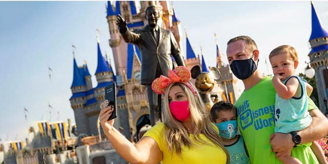 Guests stop to take a selfie at Magic Kingdom Park at Walt Disney World Resort on July 11, 2020 in Lake Buena Vista, Florida. (Photo by Matt Stroshane/Walt Disney World Resort via Getty Images)