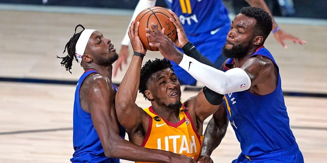 In this Aug. 30, 2020, file photo, Utah Jazz's Donovan Mitchell, center, goes up to shoot as the Denver Nuggets' Jerami Grant, left, and Paul Millsap, right, defend during the second half of an NBA basketball first-round playoff game in Lake Buena Vista, Fla. Mitchell agreed Nov. 22, 2020, to a five-year, $163 million extension to remain with the Jazz. (AP Photo/Ashley Landis, File)