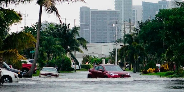 A car navigates a flooded street in the Melrose Manors neighborhood west of downtown Fort Lauderdale on Monday, Nov.9, 2020.