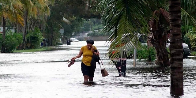 A woman crosses through floodwaters in the Melrose Place neighborhood in Fort Lauderdale, Fla., on Monday, Nov. 9, 2020.