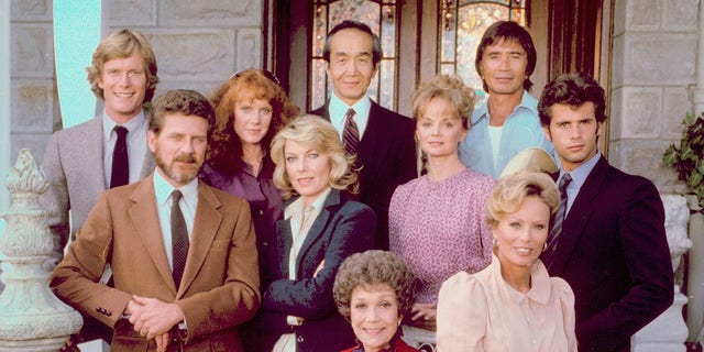 The cast of 'Falcon Crest,' clockwise from front center: Jane Wyman, Robert Foxworth, William R. Moses, Jamie Rose, Chao Li Chi, Nick Ramus, Lorenzo Lamas, Abby Dalton (sitting on arm of chair), Margaret Ladd (middle row), and Susan Sullivan. (Photo by CBS Photo Archive/Getty Images)