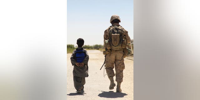 我们. Marine Cpl. Christopher Mullins with H&安培;S Company, 1st Battalion, 5th Marines (1/5) patrols through the Nawa bazaar with a Afghan boy in Nawa District, Helmand Province, Afghanistan on Sept. 08, 2009 (U.S Marine Corps photo by Lance Cpl. Jeremy Harris/Released)