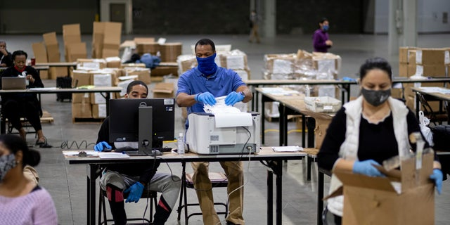 Workers scan ballots as the Fulton County presidential recount gets under way Wednesday morning, Nov. 25, 2020 at the Georgia World Congress Center in Atlanta. (AP Photo/Ben Gray)