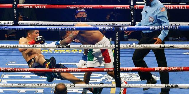 Gervonta Davis, right, pushes Leo Santa Cruz down during a boxing bout Saturday, Oct. 31, 2020, in San Antonio. (AP Photo/Ronald Cortes)