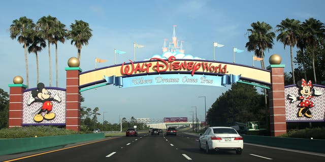 Visitors drive past a sign welcoming them to Walt Disney World on the first day of reopening of the iconic Magic Kingdom theme park in Orlando, Florida, on July 11, 2020. (Gregg Newton / Gregg Newton / AFP)
