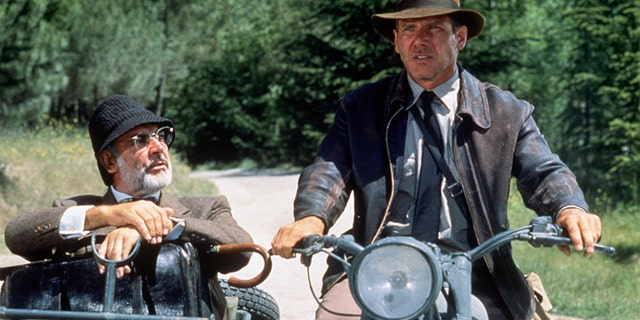 """American actor Harrison Ford as the eponymous archaeologist and Scottish actor Sean Connery as his father, Henry Jones, during the motorcycle chase scene from the film """"Indiana Jones and the Last Crusade"""" 에 1989"""