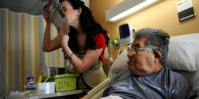 Gina Elise, Founder of the non-profit organization, Pin-Ups For Vets, kisses the calendar she is giving to Army veteran Manuel Olveda 84, during her visit to the Denver VA Medical Center Wednesday, December 14, 2011.