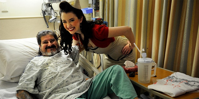 Tito Suazo, who served in the Air Force, gets a hug from Gina Elise, Founder of the non-profit organization, Pin-Ups For Vets, during her visit to the Denver VA Medical Center Wednesday, December 14, 2011.