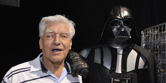 "English actor David Prowse, who played the character of Darth Vader in the first ""Star Wars"" trilogy, poses with a fan dressed up in a Darth Vader costume during a Star Wars convention on April 27, 2013 in Cusset, France. (Getty Images)"