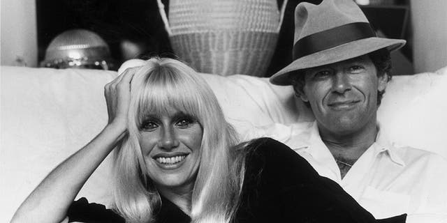 Suzanne Somers and her husband, Canadian television show host Alan Hamel, sitting on a sofa in their home, Hollywood, Calif., early 1980s.