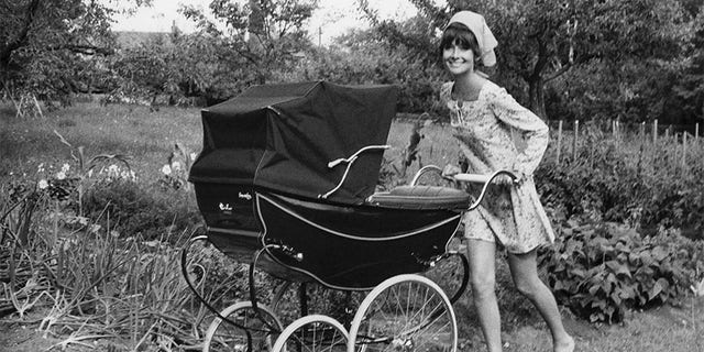 Audrey Hepburn pushing her son Luca, Sean's younger brother, in a carriage.
