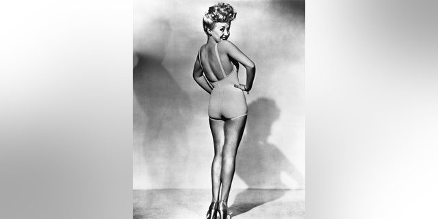 Popular American movie actress Betty Grable models a bathing suit in the most famous pinup photo of World War II.