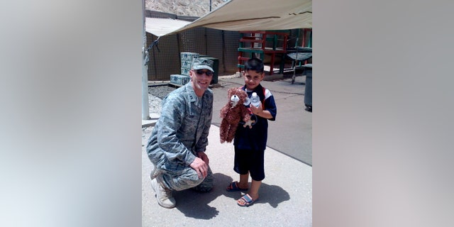 Chaplain Cizek handing out stuffed animal to Iraq child